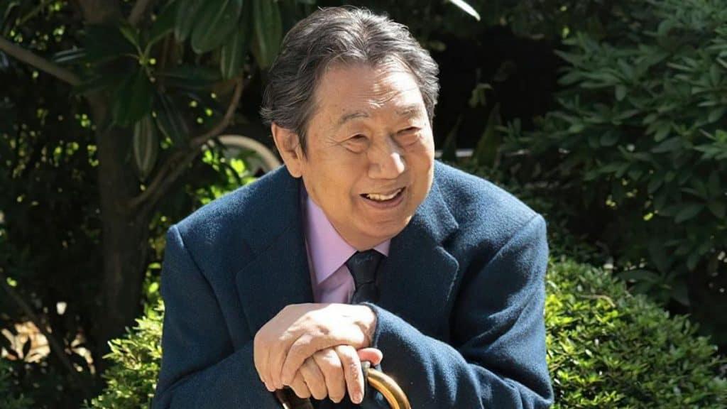 """Shunsuke Kikuchi, compositor de trilhas sonoras de """"Dragon Ball"""" e """"Kamen Rider"""", é mostrado na imagem, sentado e apoiando as mãos em uma bengala. Ele veste um paletó e gravata azul-marinho, com uma camisa rosa."""
