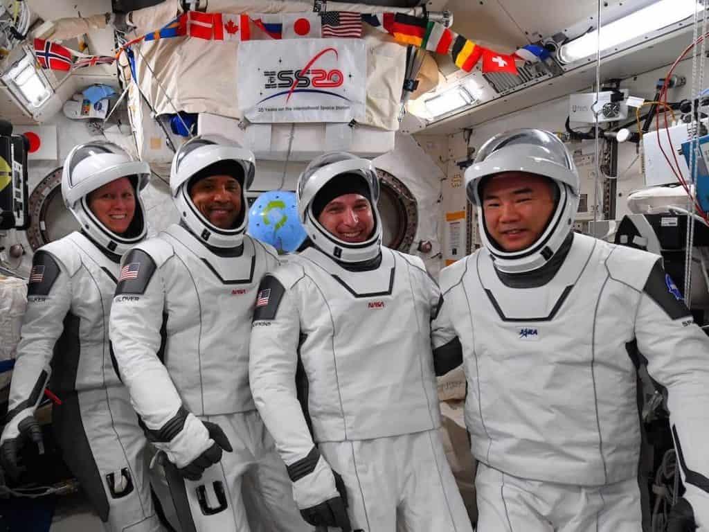 Astronautas da Crew-1 posam com seus trajes espaciais antes da realocação da Resilience. Da esquerda para a direita: Shannon Walker, Victor Glover, Mike Hopkins e Soichi Noguchi.