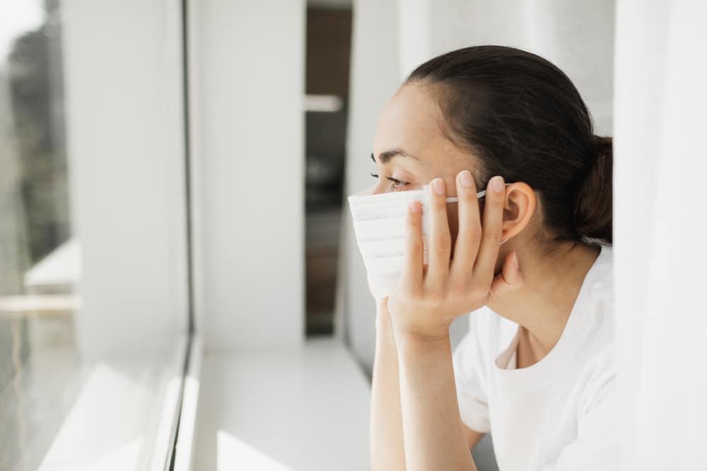 Mulher de máscara em frente a janela