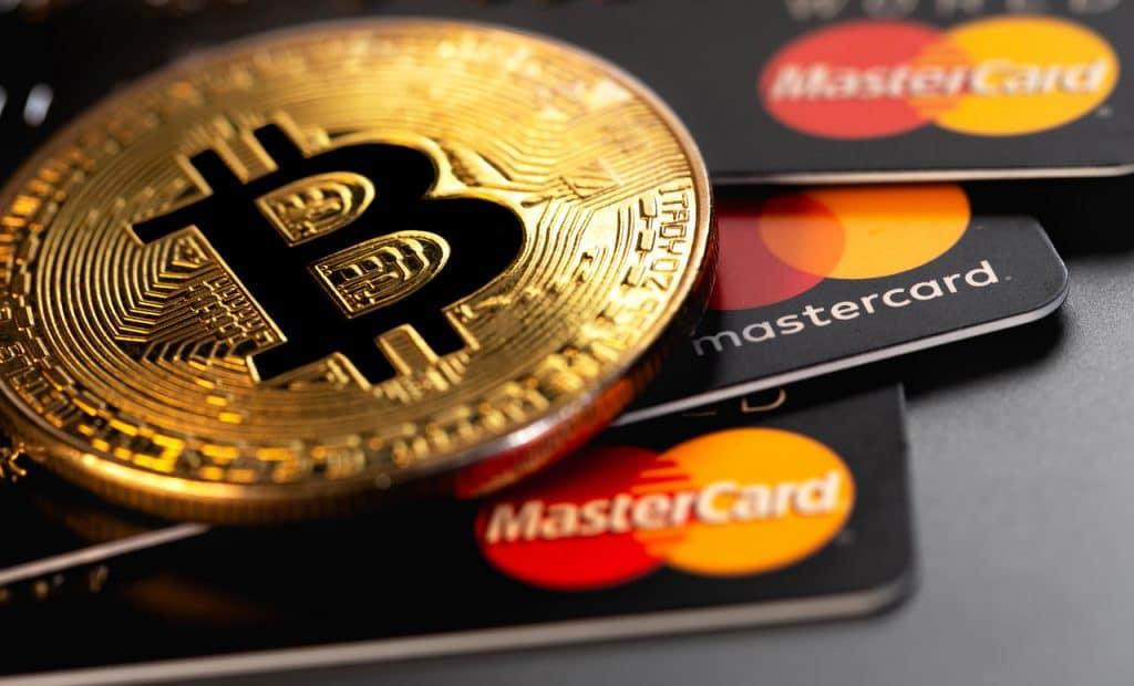 Cartões da Mastercard e uma moeda ilustrando o bitcoin