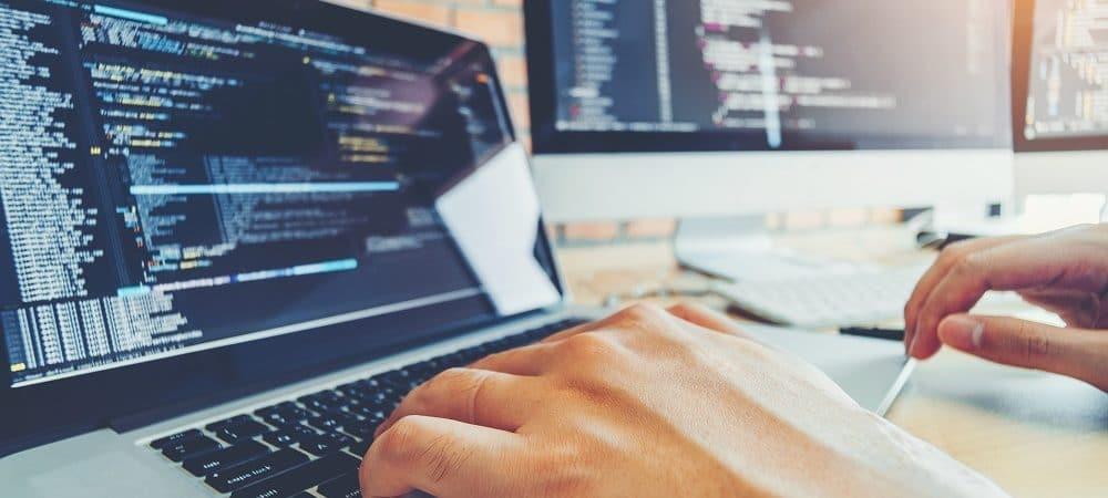 Imagem mostra uma mão digitando um código de programação em um teclado de notebook, ao lado a tela de um iMac.