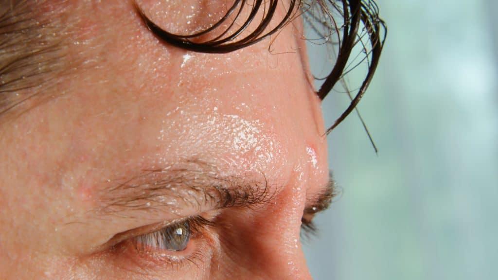 Homem com suor escorrendo na testa'