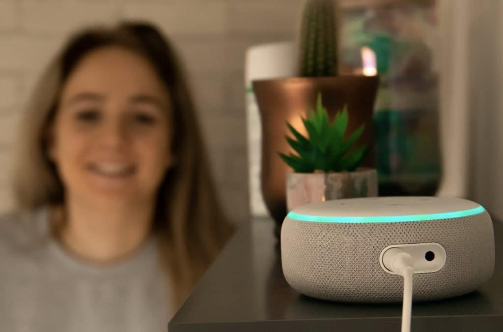 Imagem mostra caixa de som Amazon Echo em primeiro fundo e mulher ao fundo, sugerindo interação entre ambos