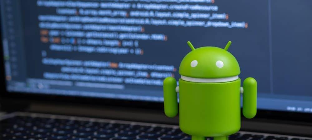 Um boneco do sistema Android foi colocado em cima de um teclado de notebook; ao fundo é possível ver a tela do dispositivo exibindo uma porção de códigos