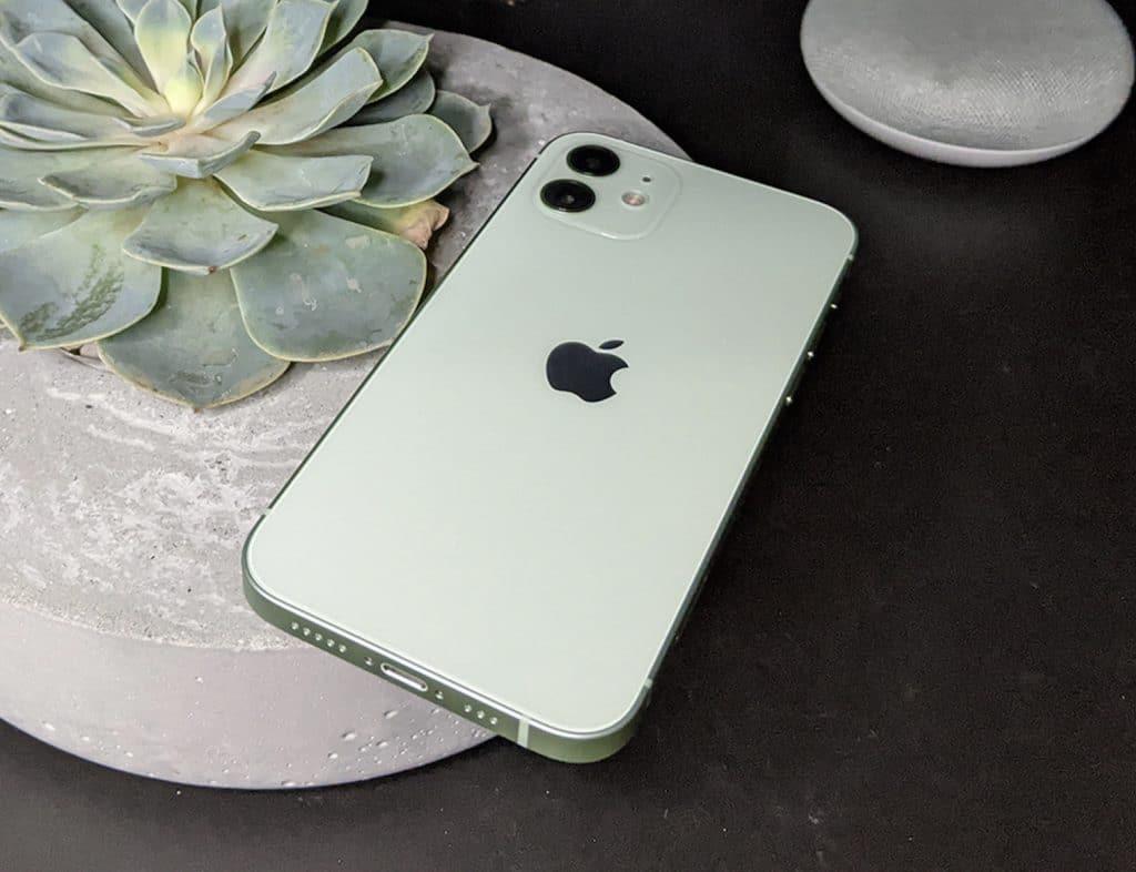 Foto do iPhone 12, posicionado com a tela para baixo em cima de uma mesa para destacar seu conjunto de câmeras