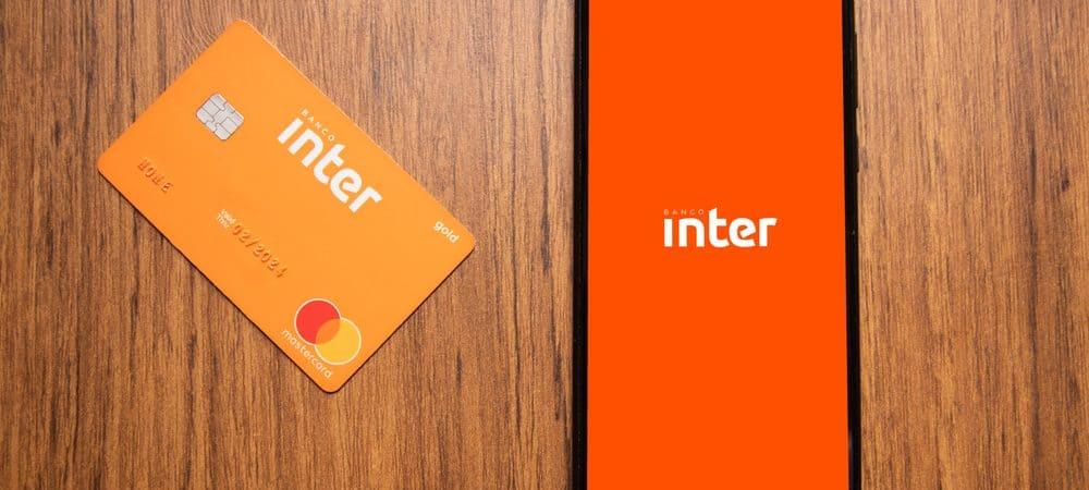 Em uma superfície de madeira, há um cartão do Banco Inter e, ao lado, um smartphone exibindo o logo do mesmo banco na tela.