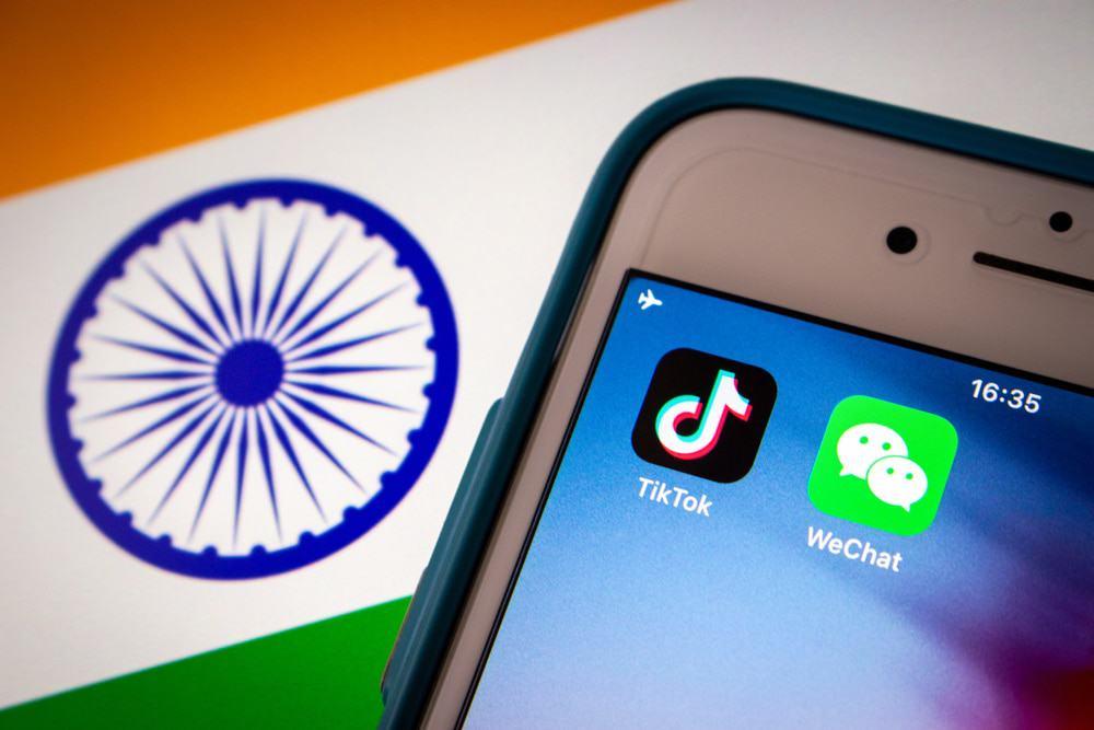 Imagem mostra, ao fundo, a bandeira da Índia; à frente um smartphone exibe dois ícones de aplicativos, entre eles o TikTok.