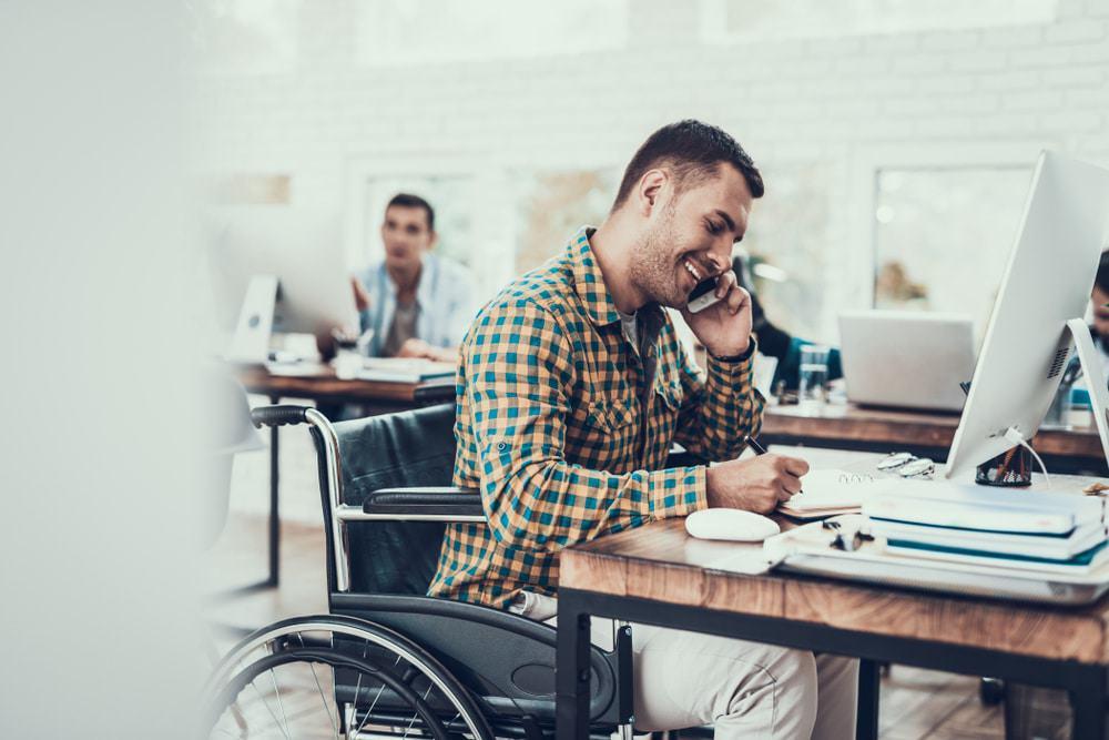 PCD na cadeira de rodas está alocado em uma mesa, mexendo no computador e falando ao telefone
