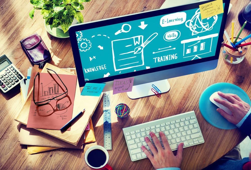 Imagem ilustra treinamento e capacitação em tecnologia, com uma mesa cheia de papeis e um monitor acompanhado de mouse e teclado.