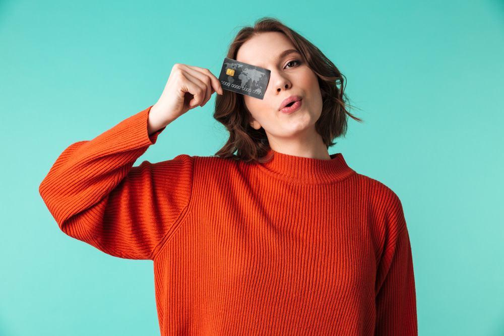 A imagem com um fundo verde claro mostra uma jovem de blusa laranja, segurando um cartão de crédito na mão, tapando um dos olhos.