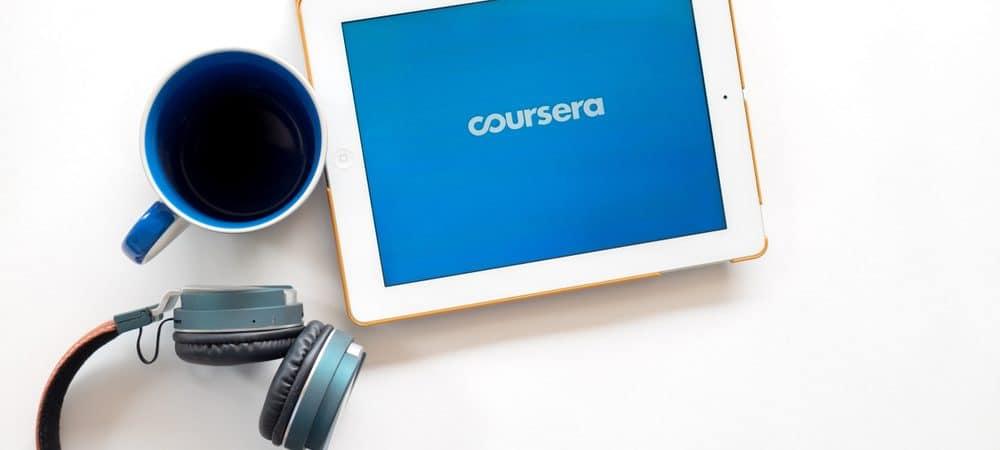 Em uma superfície estão um fone de ouvido headset, uma canela e um tablet com o logo da edtech Coursera na tela.