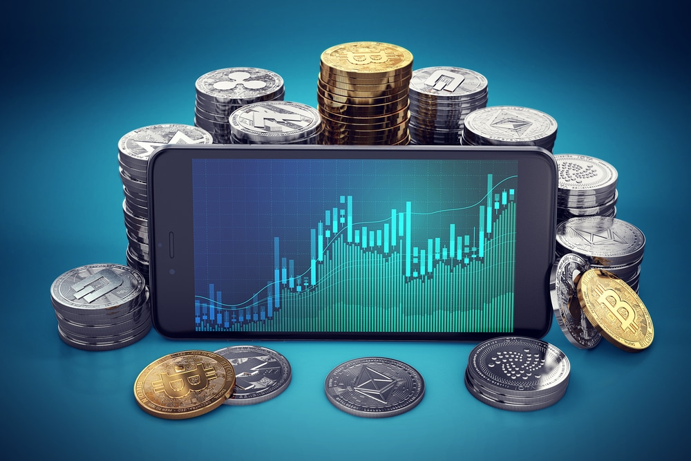Imagem exibe um celular com a tela cheia de gráficos; ao fundo, pilhas de diferentes criptomoedas