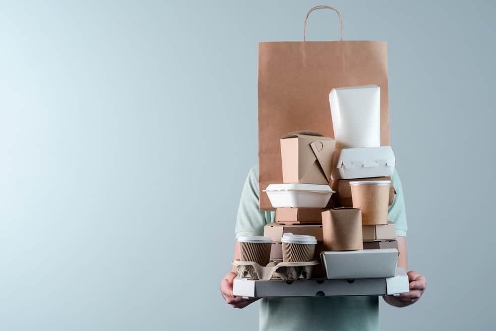 Imagem mostra uma pessoa carregando várias embalagens de delivery de comida.