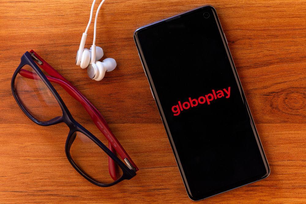 Sobre uma mesa de madeira, um smartphone exibe o logotipo do Globoplay, ao lado há óculos de grau e um fone de ouvido.