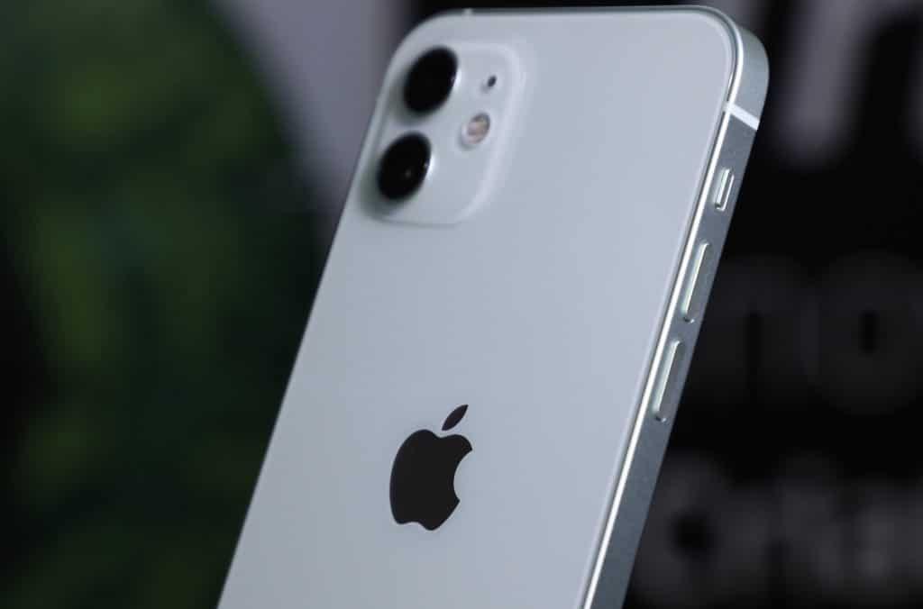 Imagem mostra um iPhone 12 na cor branca, exibido pelas costas, com o logo da Apple e a câmera em evidência.  Apple pode inserir lente periscópica na câmera do próximo iPhone, segundo patente