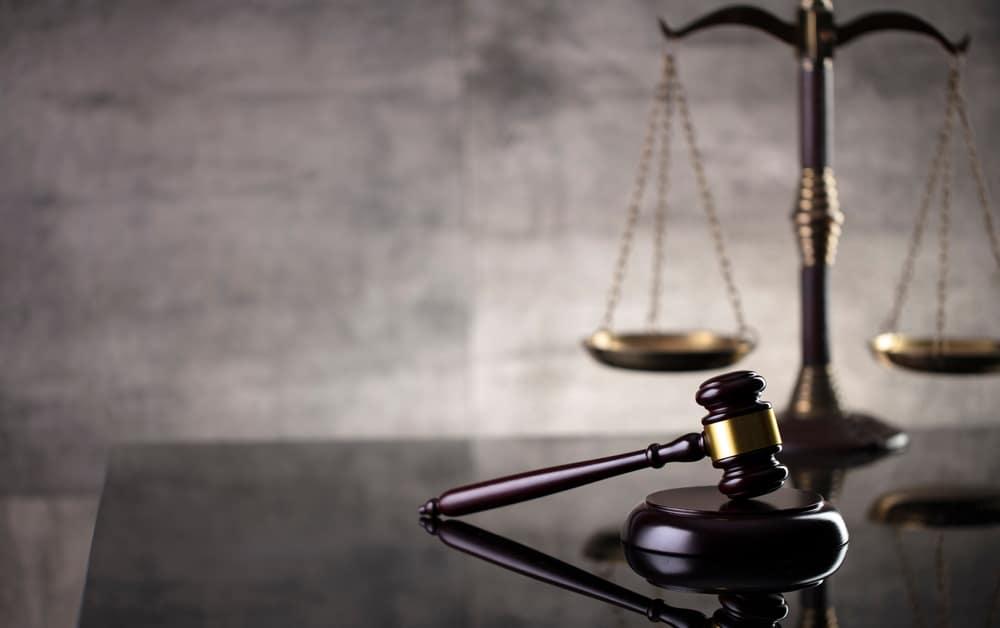 Imagem mostra, sobre uma superfície, o martelo de juiz e uma balança da justiça.