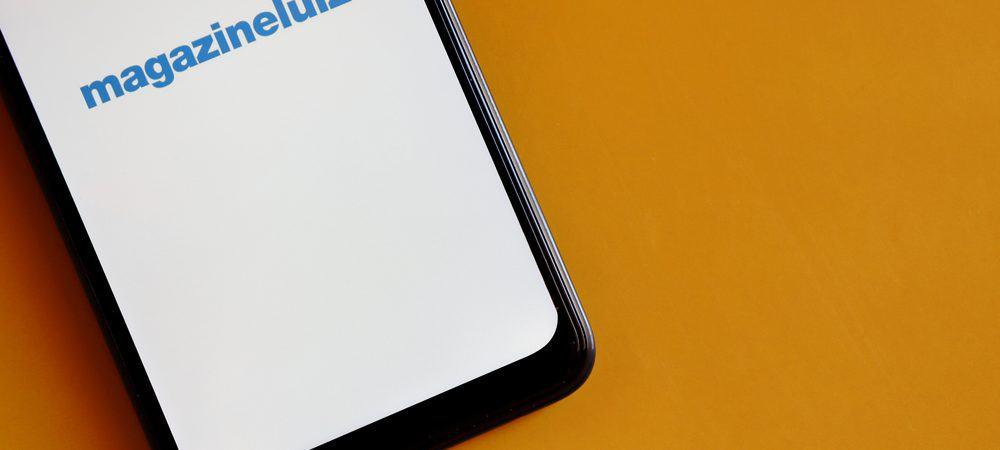 Em uma superfície amarela, um smartphone exibe em sua tela o logo da Magazine Luiza, ou Magalu