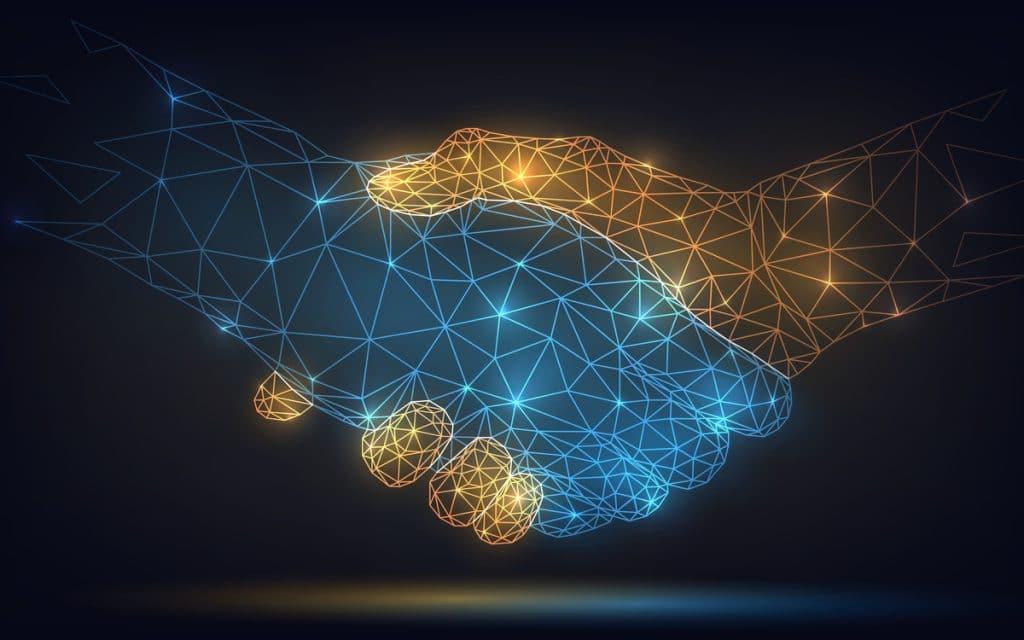 A imagem, de fundo escuro, mostra a ilustração de um aperto de mãos, uma azul e outra amarela; ambas as mãos foram digitalmente desenhadas e são preenchidas com linhas que formam redes luminosas.