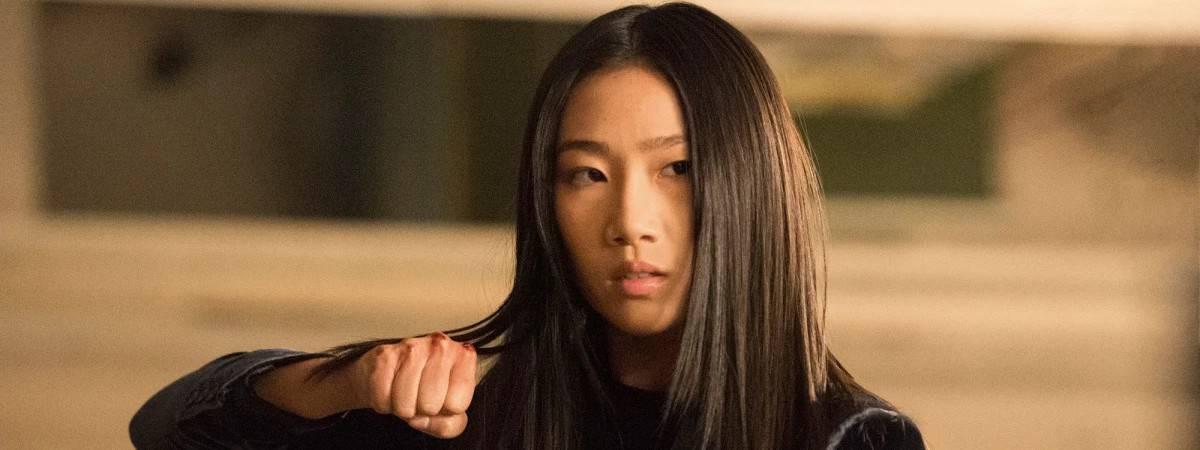 Imagem mostra a atriz Olivia Luang, em pose de luta para sua personagem na série
