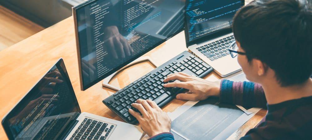 Homem sentado em uma mesa com três notebooks, programando