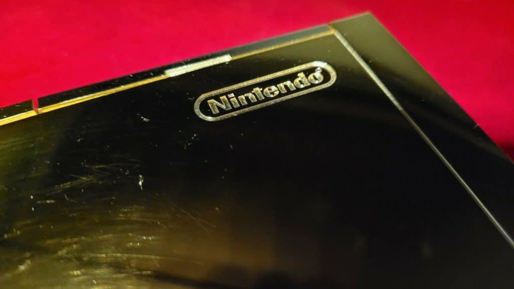 Imagem mostra detalhe do Wii de ouro, com a logomarca da Nintendo em destaque