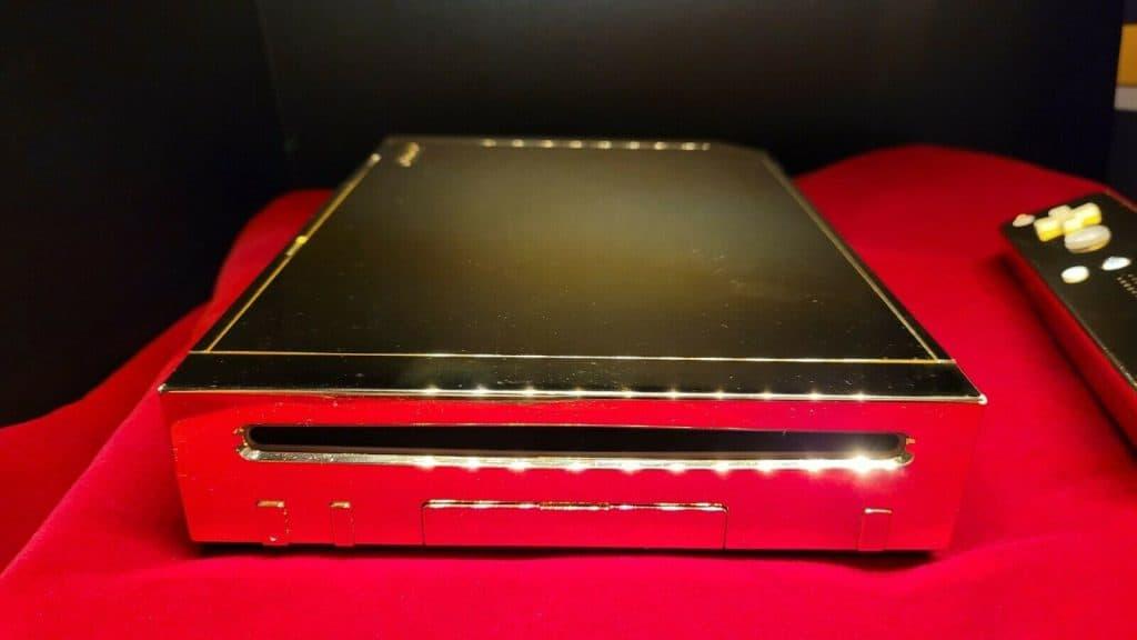 """Imagem mostra o """"Wii de ouro da Rainha"""", versão especial do console da Nintendo feita em ouro 24 quilates, sob uma mesa"""