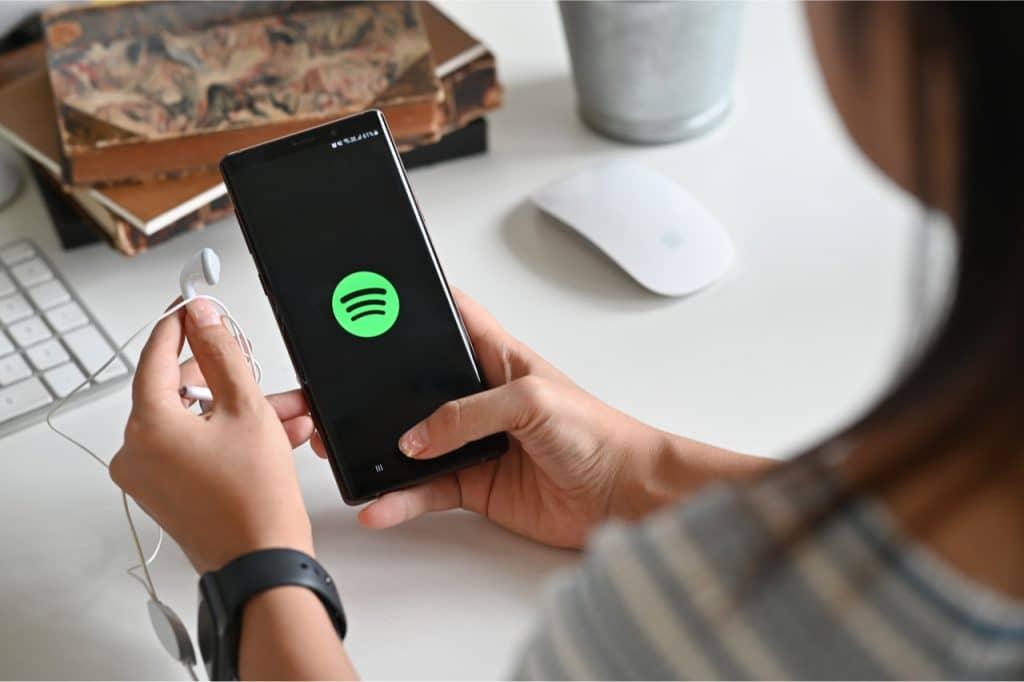 Imagem mostra uma mulher usando o Spotify pelo celular. Empresa teve aumento de usuários e faturamento no primeiro trimestre de 2021.