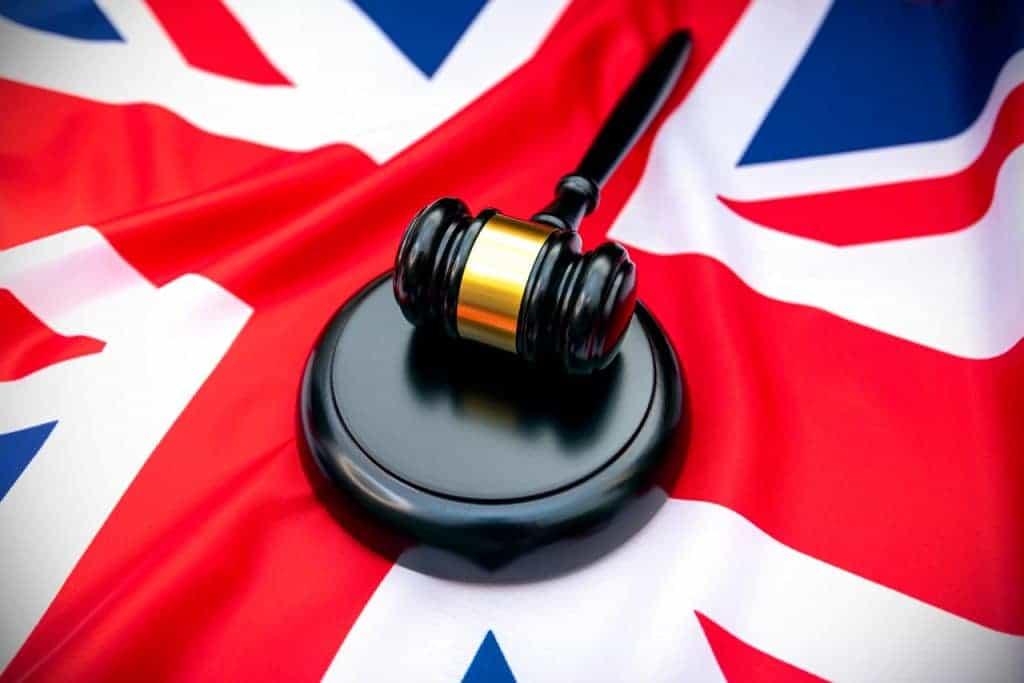 Martelo de tribunal em cima de uma bandeira do Reino Unido
