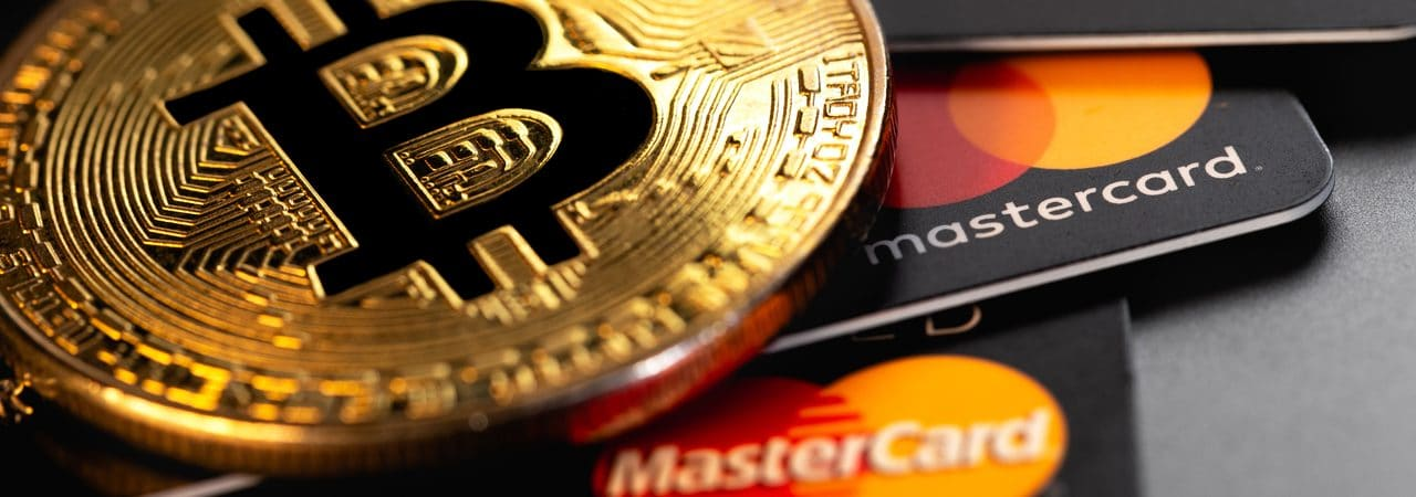 Cartões da Mastercard embaixo de uma moeda do bitcoin