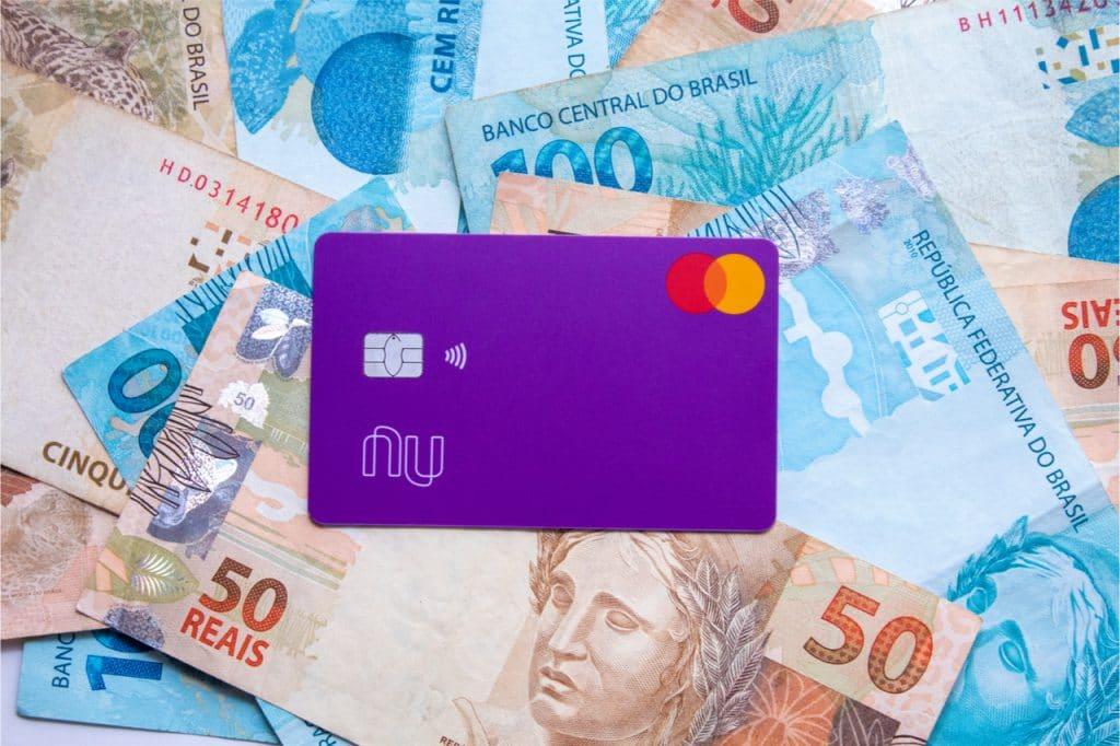 Imagem mostra um fundo com notas de 50 e 100 reais, com o cartão do Nubank à frente. Rumores falam em abertura de capital da empresa