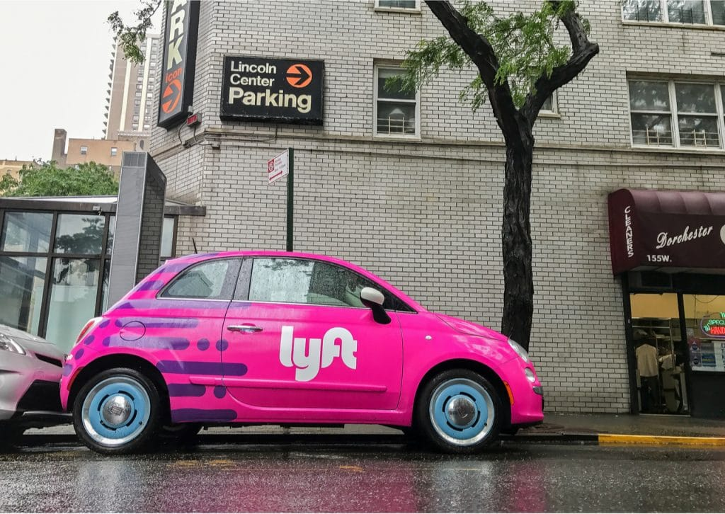 Lyft's decision to sell autonomous driving division should help the company achieve profitability ahead of time. In the image: A Lyft car parked on a tree-lined street in New York