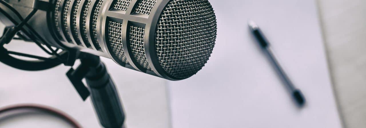 Spotify lança plataforma de assinatura para podcasts, competindo com a Apple. Na imagem: um microfone de podcast, com uma caneta e papel de anotações ao fundo