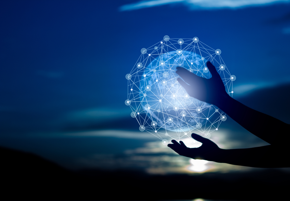 Image illustrates digital transformation through a silhouette of two hands holding a globe made of digital networks