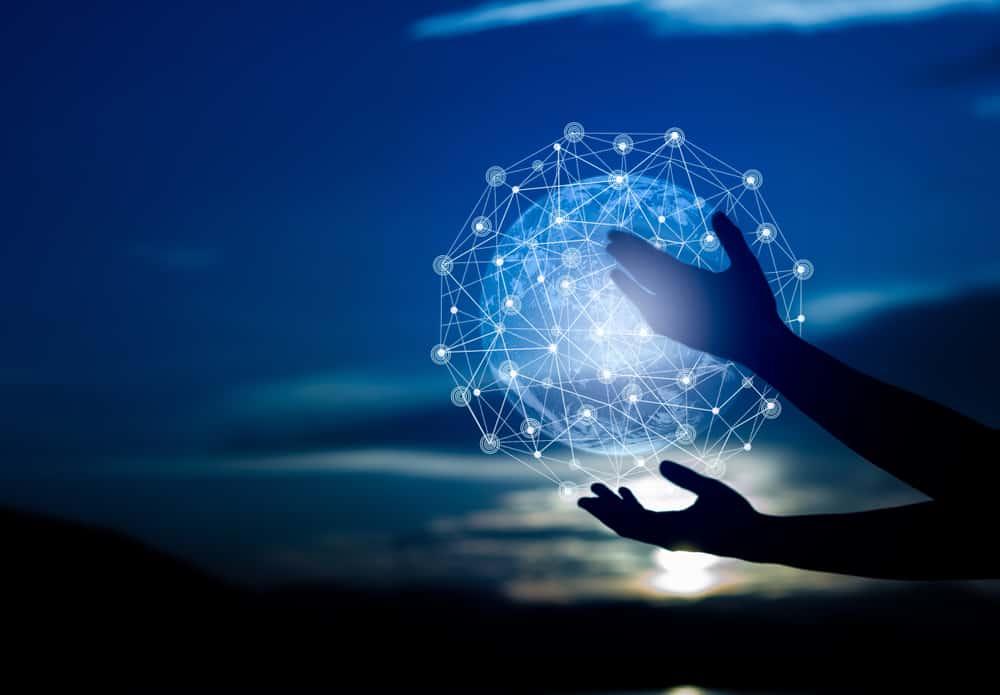 Imagem ilustra a transformação digital por meio de uma silhueta de duas mãos segurando um globo feito de redes digitais
