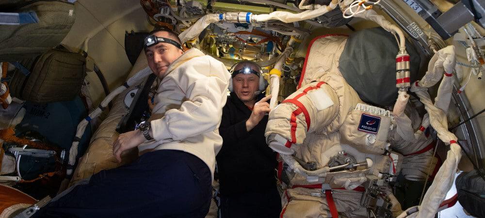 Pyotr Dubrov (à esquerda) e Oleg Novitskiy preparam trajes espaciais russos Orlan para uma caminhada espacial