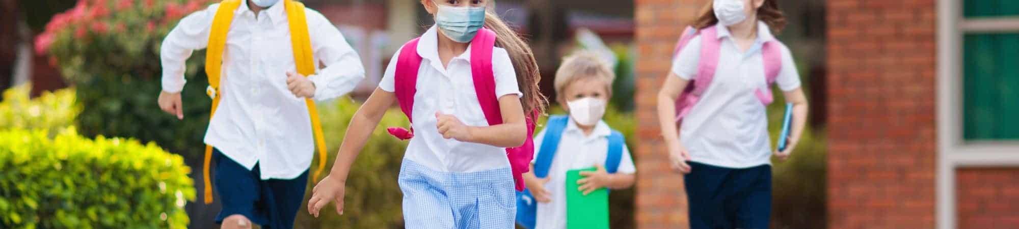 crianças de máscara correndo na escola
