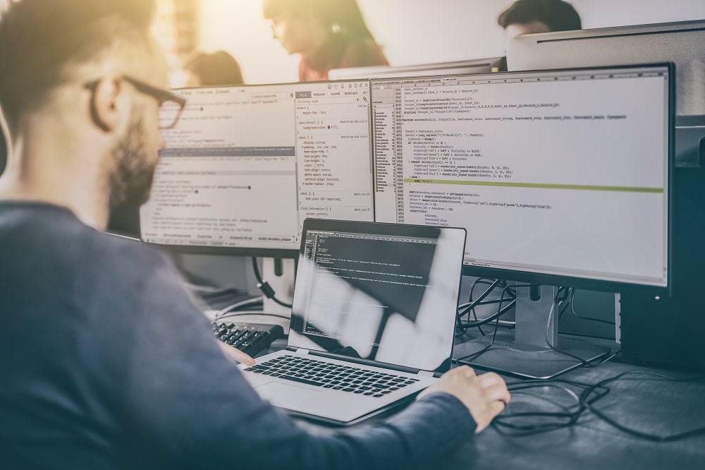 Imagem mostra um desenvolvedor escrevendo linhas de código no computador