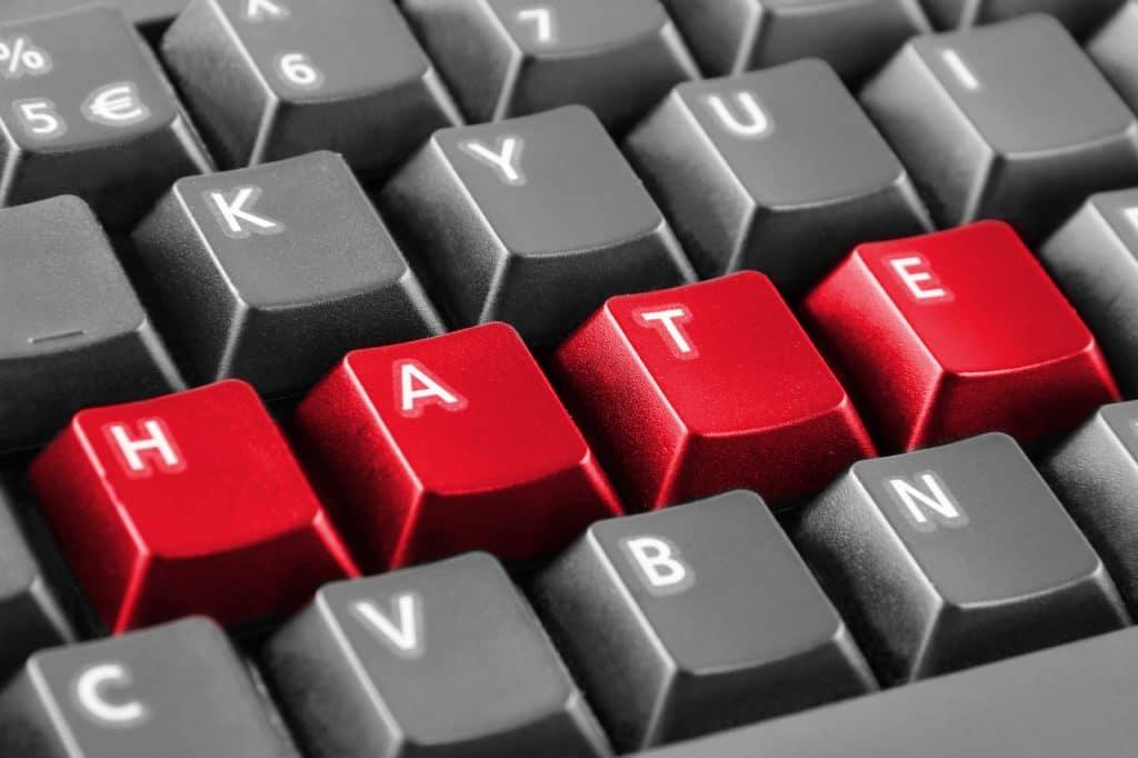 """Ilustração de um teclado formando a palavra """"hate"""" (""""ódio"""", traduzido para o português)"""