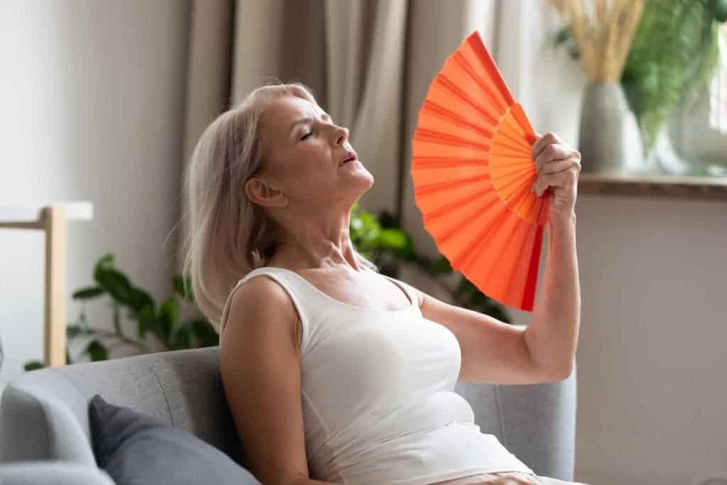mulher se abanando pelo calor da menopausa