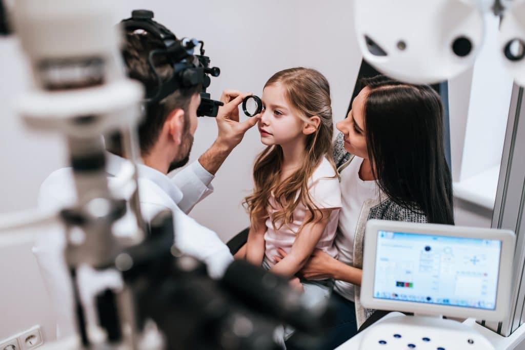 Criança sendo examinada por um oftalmologista