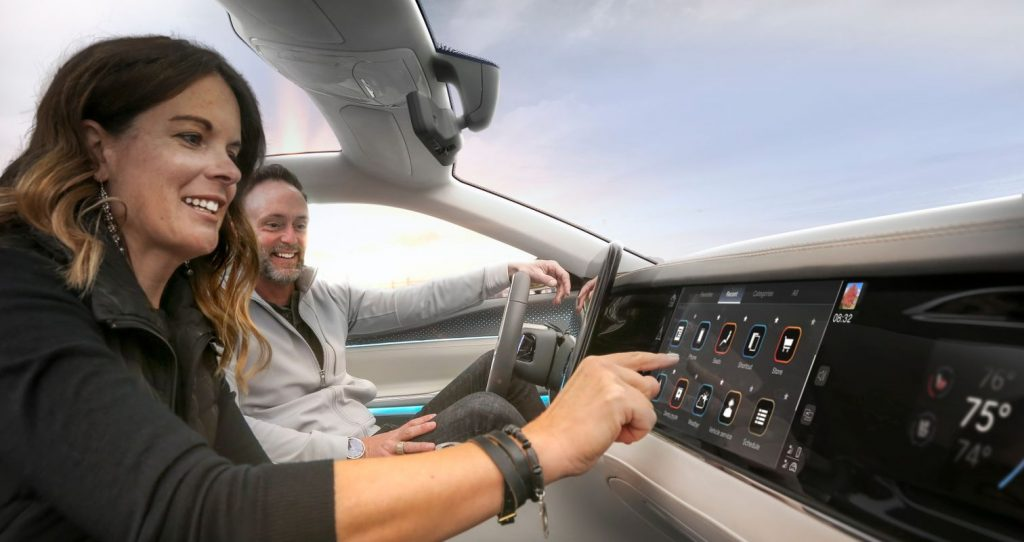 Usuários observam painel inteligente de carro.