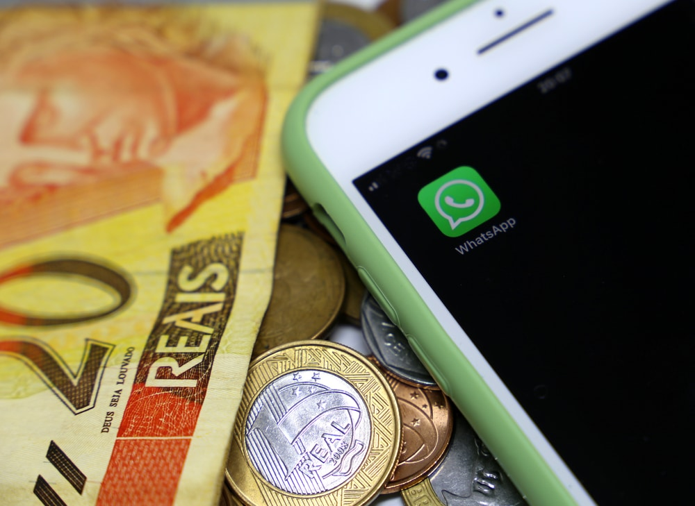 Logo do WhatsApp ao lado de notas de dinheiro