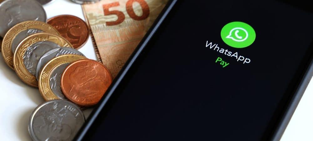 Celular com a logo do WhatsApp Pay ao lado de moedas e uma nota de 50 reais