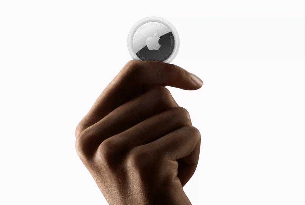 A segurança da AirTag, da Apple, pode até funcionar na emissão de alertas, mas não ajudam a prevenir casos de perseguição e stalking  Na imagem: uma AirTag, sendo segurada por uma mão à frente de um fundo branco