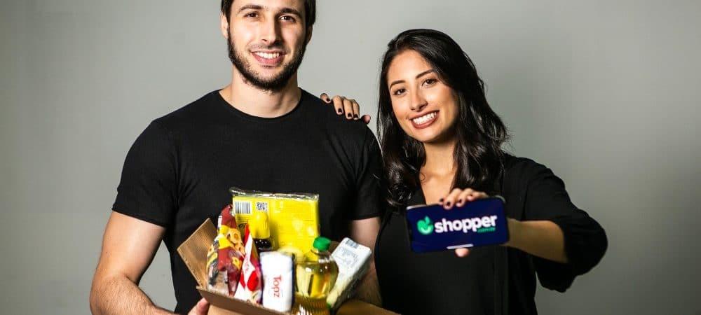 Imagem mostra os cofundadores da startup Shopper, Fábio Rodas e Bruna Vaz; Fábio segura uma caixa com produtos de supermercado, especialidade da empresa, enquanto Bruna segura um smartphone que leva o logo da empresa na tela.