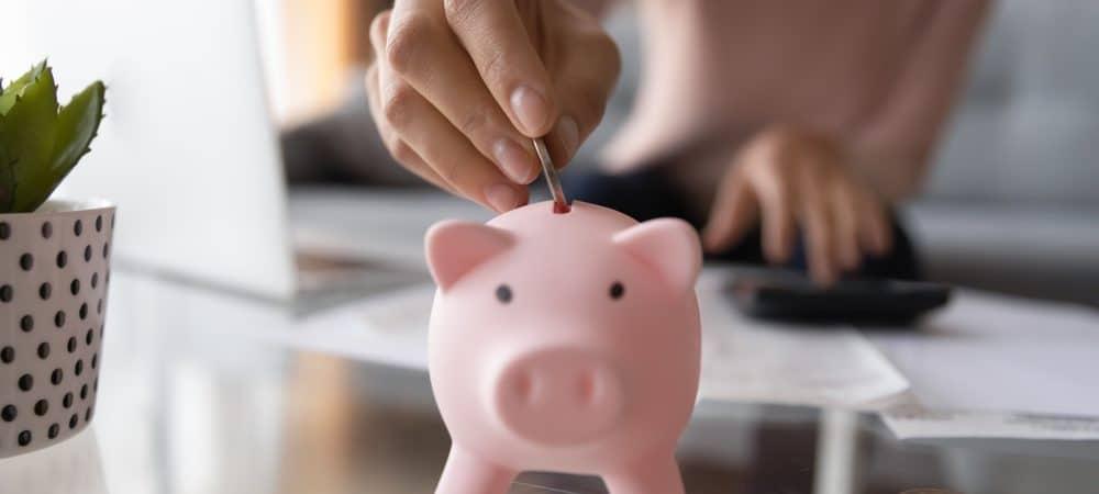 Imagem mostra uma pessoa colocando moedas em um cofre de porquinho.