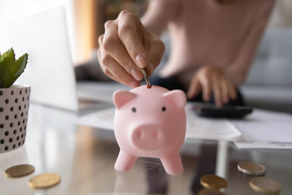 Image shows a person putting coins into a piggy bank.