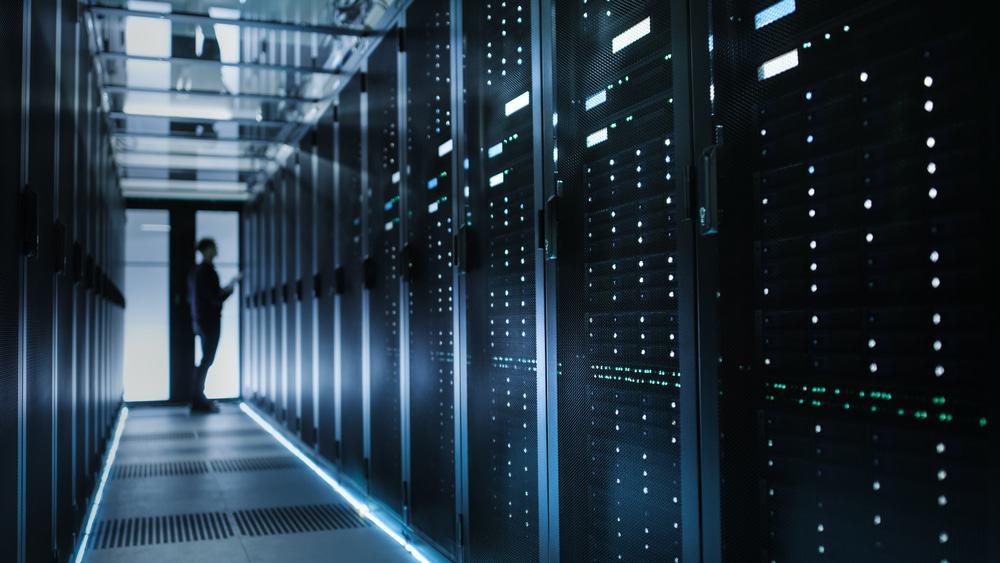 Foto do corredor de um data center; ao fundo, há a silhueta de um técnico de TI que está observando a infraestrutura tecnológica.