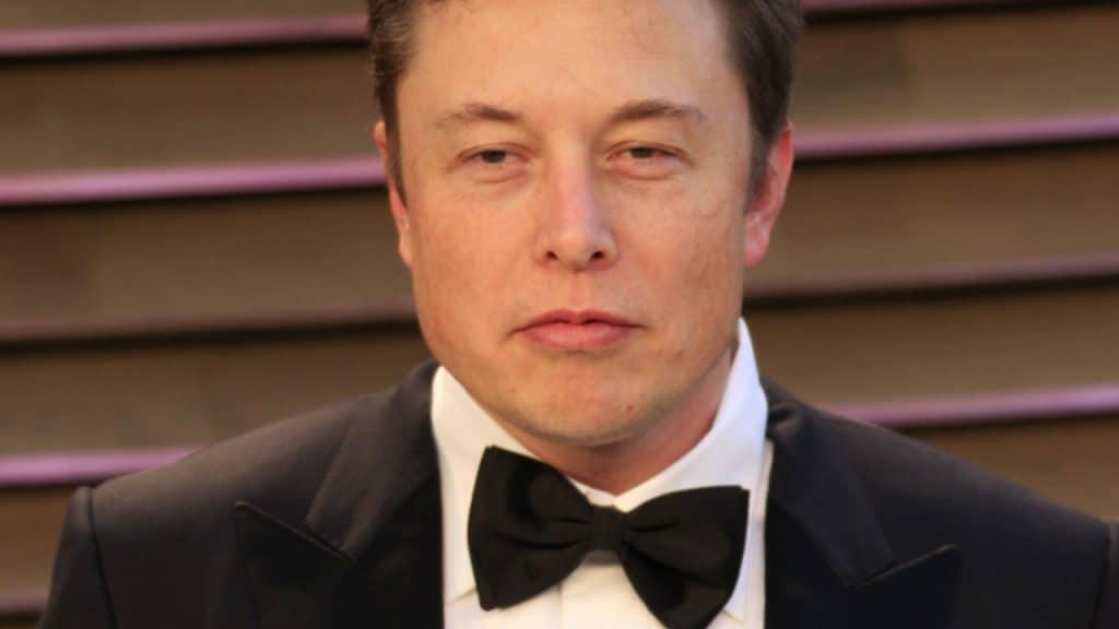 Elon Musk é exibido na imagem, usando gravata borboleta preta, paletó preto e camisa branca, em um evento de gala