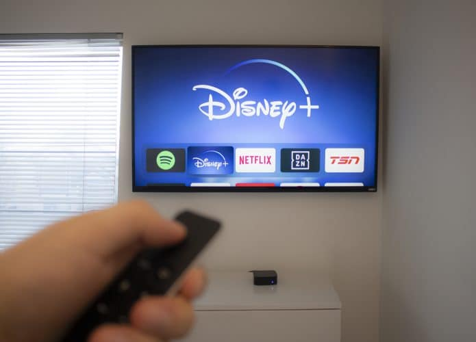 Pessoa segurando controle remoto e apontando para televisão com a plataforma de streaming Disney+ em destque